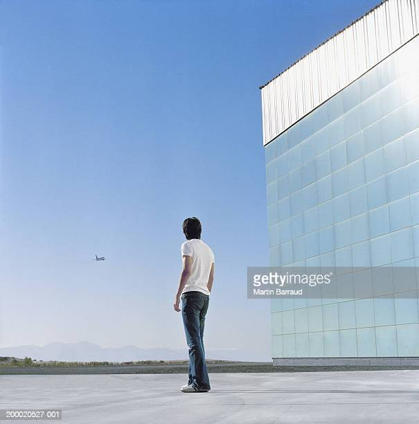 Young man beside reflective building, looking at plane, rear view