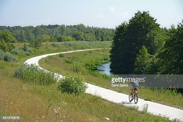 young man biking on via rhona bicycle lane - rhone stock pictures, royalty-free photos & images