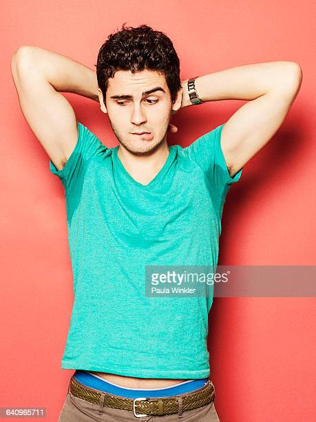 Young man biting lip while looking at sweaty armpit against red background