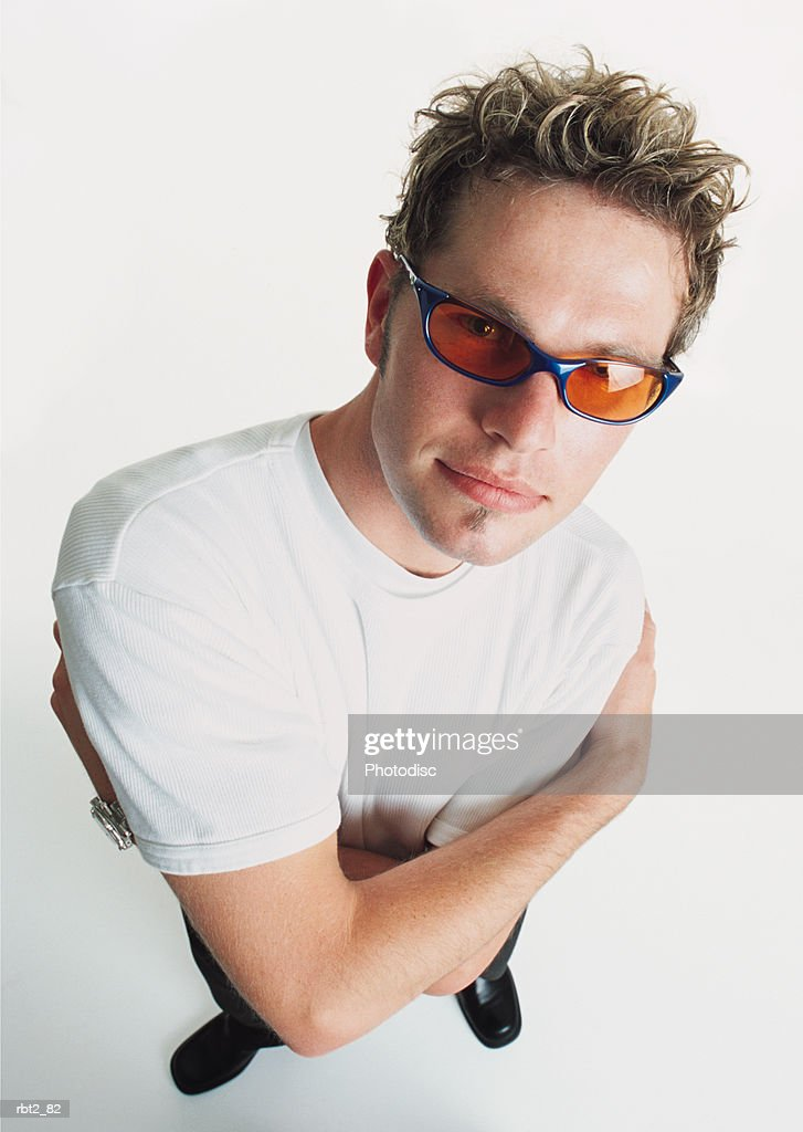 young man bleached spiked hair wears yellow sunglasses white t-shirt folds his arms looks to camera : Foto de stock