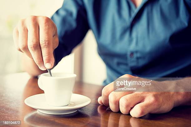 Young man blend his coffee at italian café