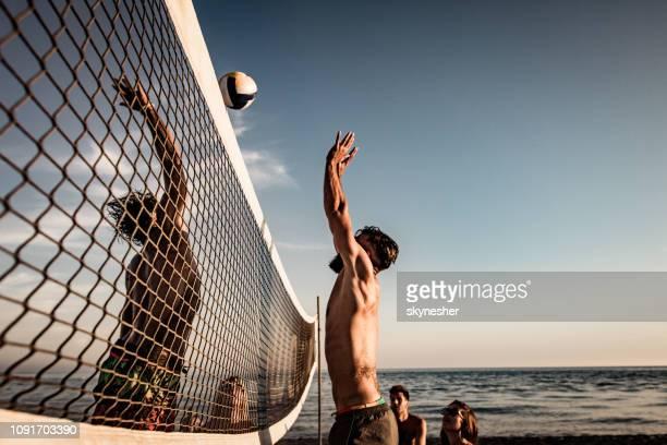 junger mann seinem freund beim spielen beach-volleyball im sommertag blockiert. - strand volleyball stock-fotos und bilder