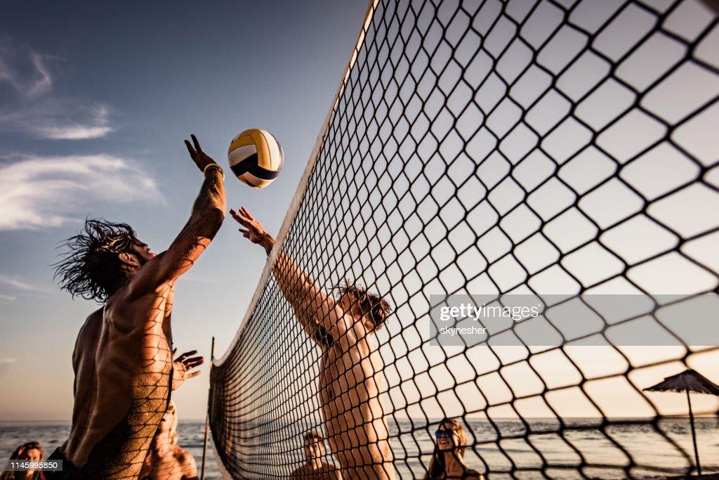 Junger Mann blockiert seinen Freund beim Beachvolleyball am Sommertag. : Stock-Foto