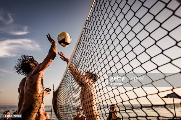 junger mann blockiert seinen freund beim beachvolleyball am sommertag. - volleyball mannschaftssport stock-fotos und bilder