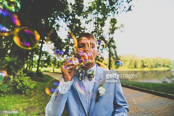 young man blowing bubbles - multi colored suit stock photos and pictures