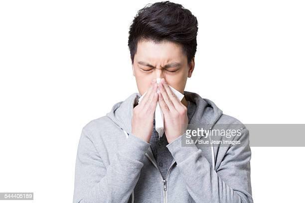 young man blowing nose - pañuelo fotografías e imágenes de stock