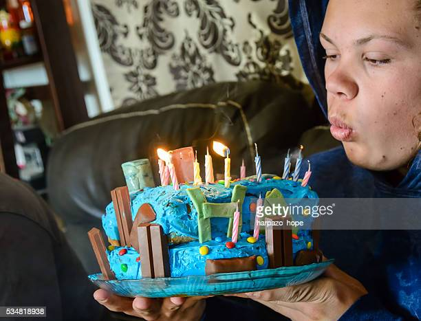 young man blowing out his birthday candles. - candle of hope imagens e fotografias de stock