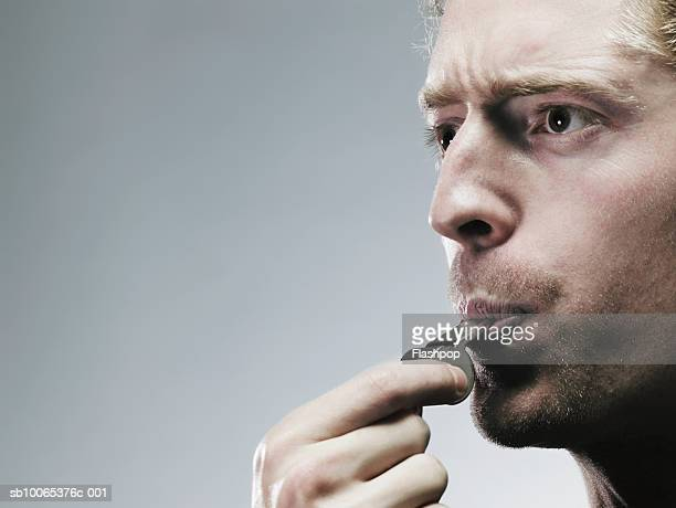 Young man blowing whistle, close-up
