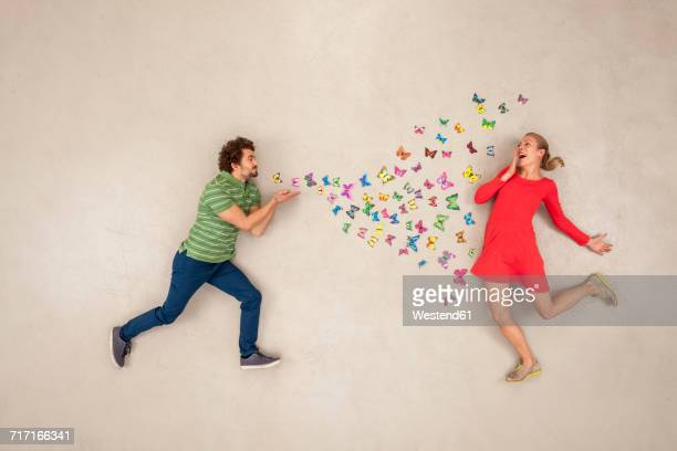 Young man blow-kissing butterflies to a woman