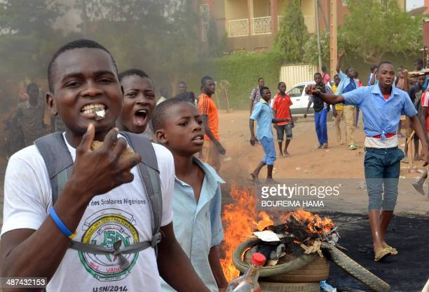 A young man blows into a whistle as others gesture next to burning tyres during a demonstration by secondaryschool and sixthform students in Niamey...