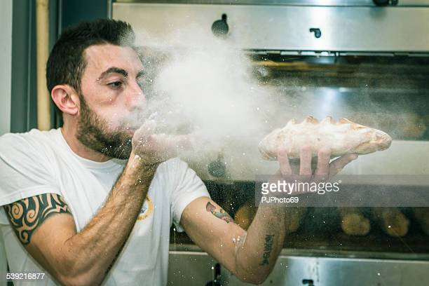 young man (baker) blows the flour on bread - pjphoto69 stock pictures, royalty-free photos & images