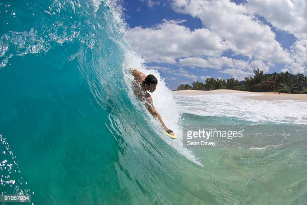 A Young Man Body Surfing At Keiki Beach On The North Shore Of Oahu Hawaii