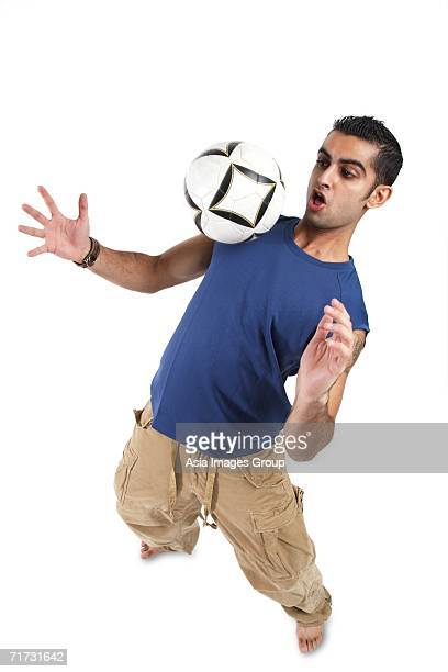 Young man bouncing soccer ball on his chest