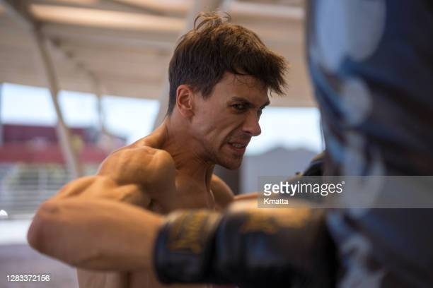 young man boxing at the punching bag. - anger stock pictures, royalty-free photos & images