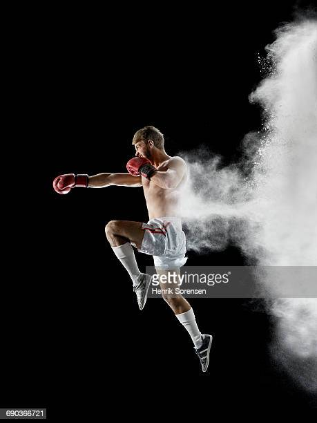young man boxing in air with white powder
