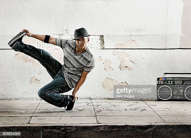 A young man breakdancing, balancing on one foot with his leg outstretched.