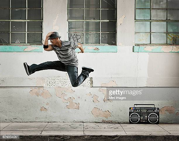 A young man breakdancing, leaping in the air doing a karate kick on a city street.