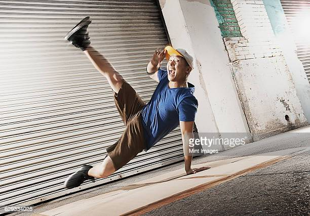 A young man breakdancing on the street of a city, balancing on one hand with his legs apart.