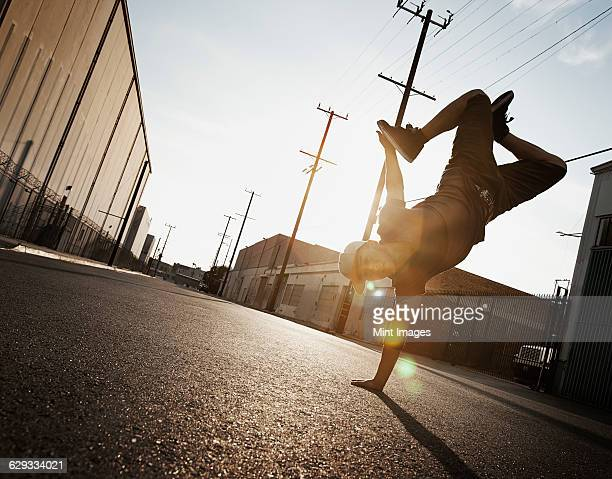 a young man breakdancing on the street of a city, doing a one handed handstand. - breakdancing stock photos and pictures