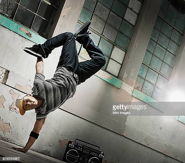 A young man breakdancing on the street of a city, doing a one handed handstand.