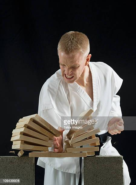 Young man breaking boards with karate chop on black background