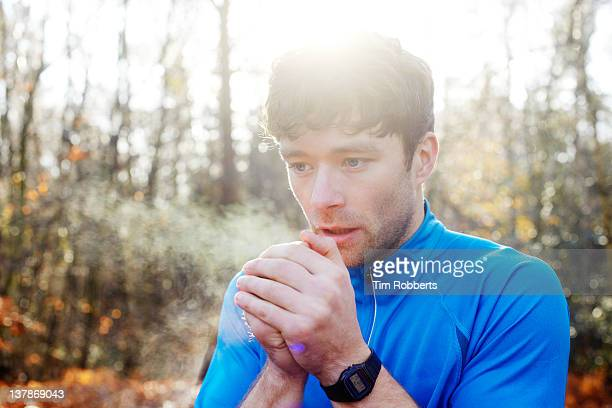 Young man breathing on hands for warmth.