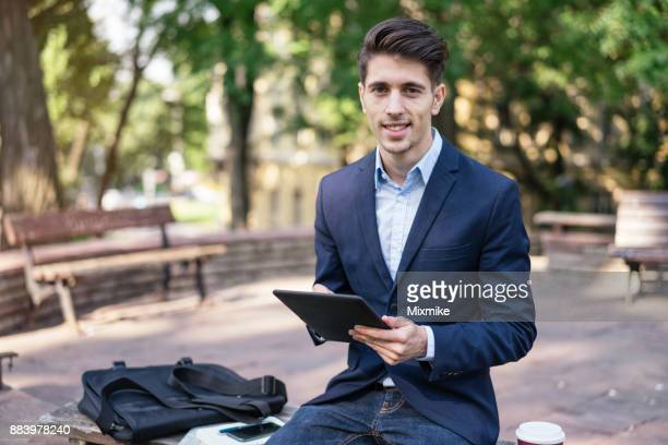Young man browsing on his tablet in the park
