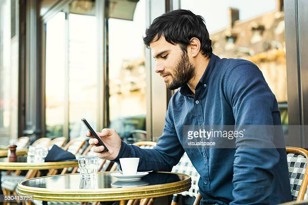 young man browsing social media in a sidewalk cafe - pavement cafe stock pictures, royalty-free photos & images