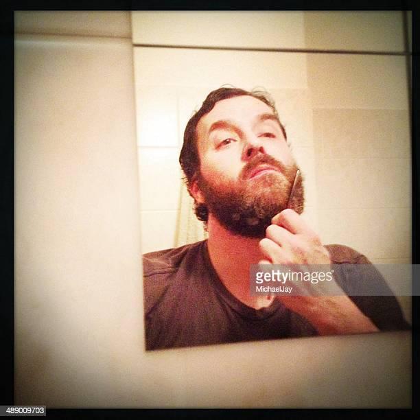 Young man brushing beard at mirror