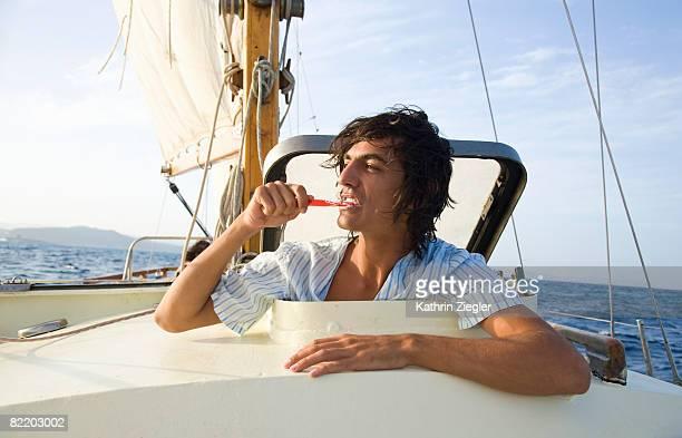 young man brushing his teeth on sailing boat