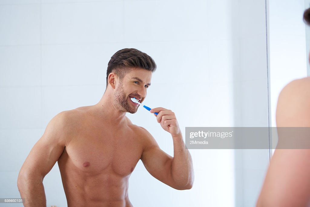 Young man brushing teeth : Stock Photo
