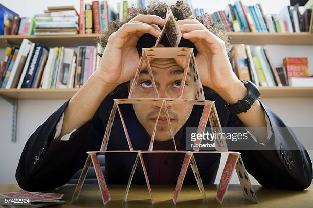 Young man building a house of cards