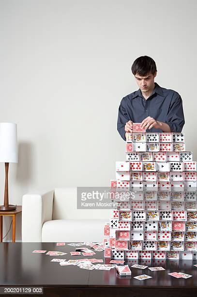 Young man building house of cards on coffee table