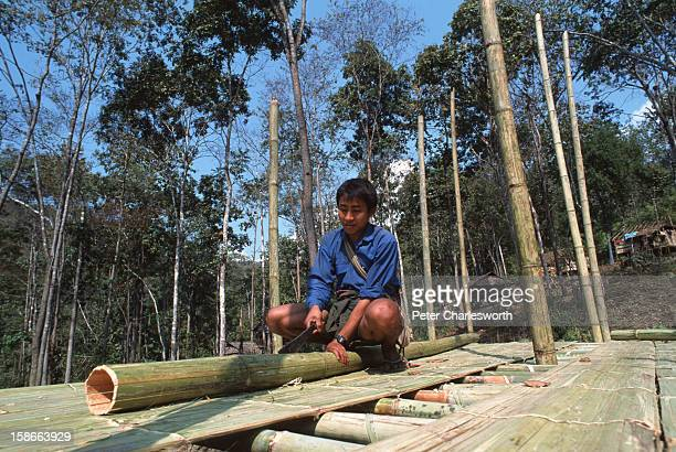 Young man builds a bamboo and leaf hut for his family in a new Karen refugee camp north of the Thai town, Mae Sot. They are recent refugee arrivals...