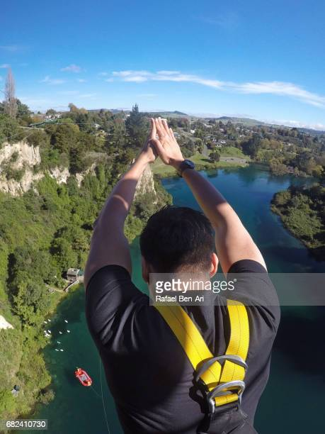 young man bungy jumps in taupo new zealand - rafael ben ari stockfoto's en -beelden