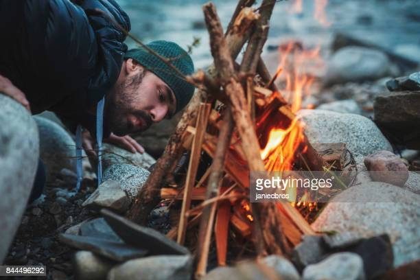 young man burning the campfire. mountainous landscape - camp fire stock photos and pictures