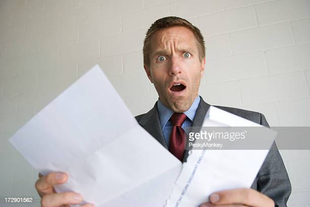 Young Man Businessman Opening Letter with Shocked Expression