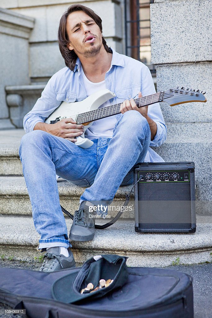 Young man busking with guitar on sidewalk : Stock Photo
