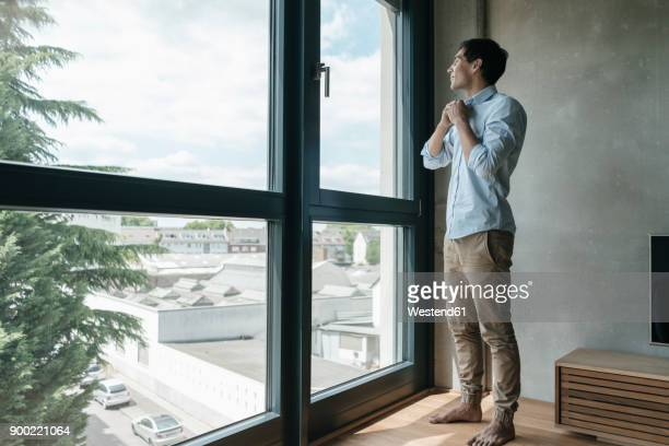Young man buttoning his shirt looking out of window