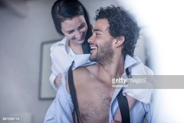 Young man buttoning his shirt while his wife watching him