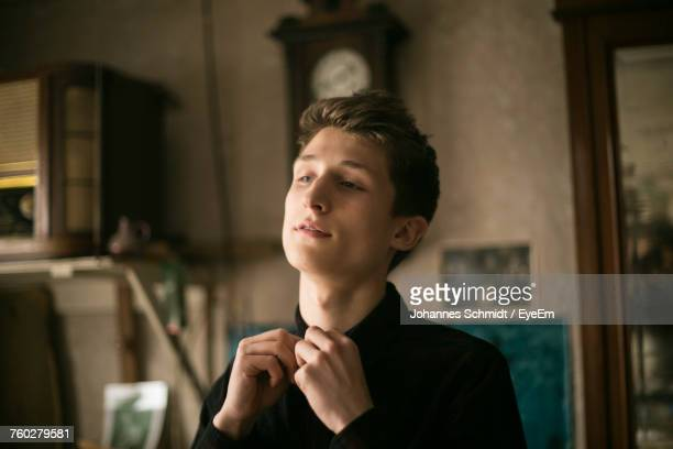 young man buttoning shirt at home - voorbereiding stockfoto's en -beelden