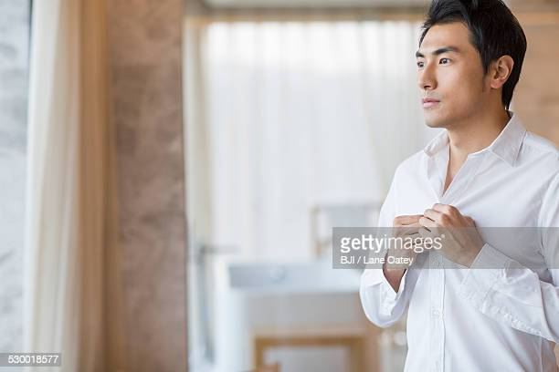 young man buttoning shirt - unbuttoned shirt stock photos and pictures
