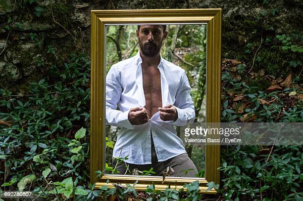 Young Man Buttoning Shirt Reflecting On Mirror