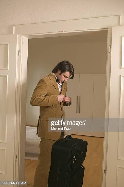 Young man buttoning up jacket by suitcase in doorway