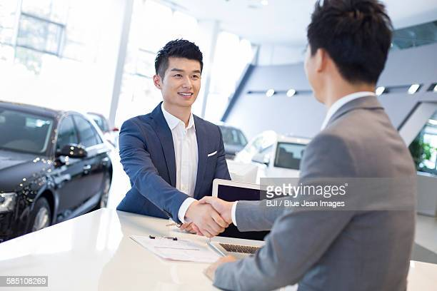 Young man buying car in showroom