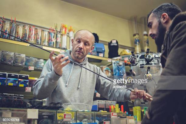 young man buying fishing rod - fishing tackle stock pictures, royalty-free photos & images
