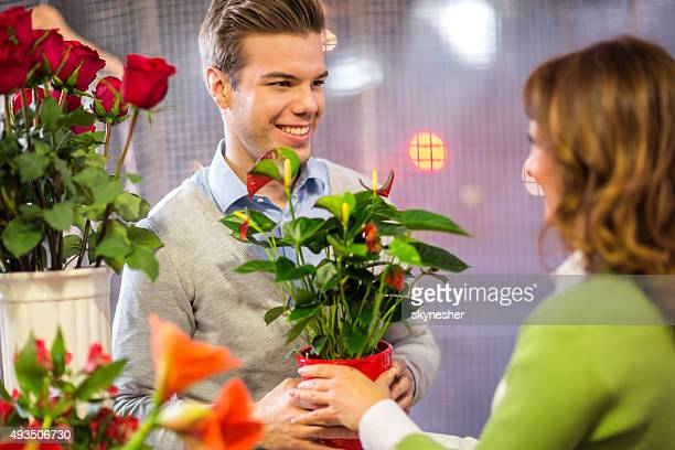 Young man buying potted plant in flower shop.