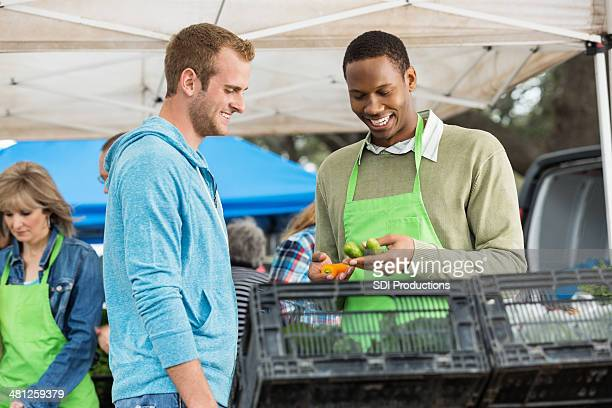 Young man buying produce from vendor at farmers market booth