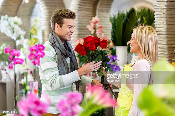 Young man buying red roses in a flower shop.