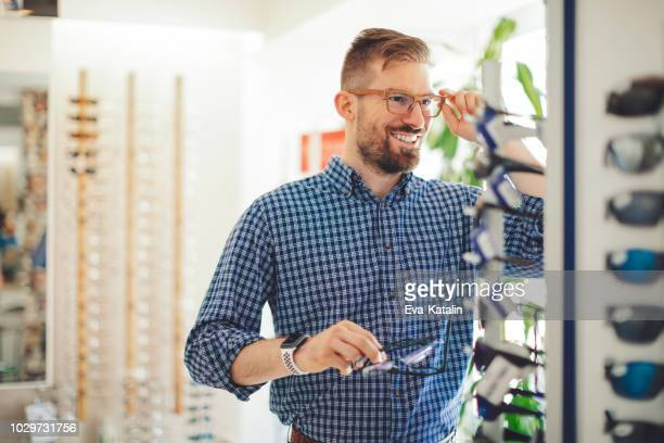 young man buying sunglasses at the optical store - optical instrument stock pictures, royalty-free photos & images